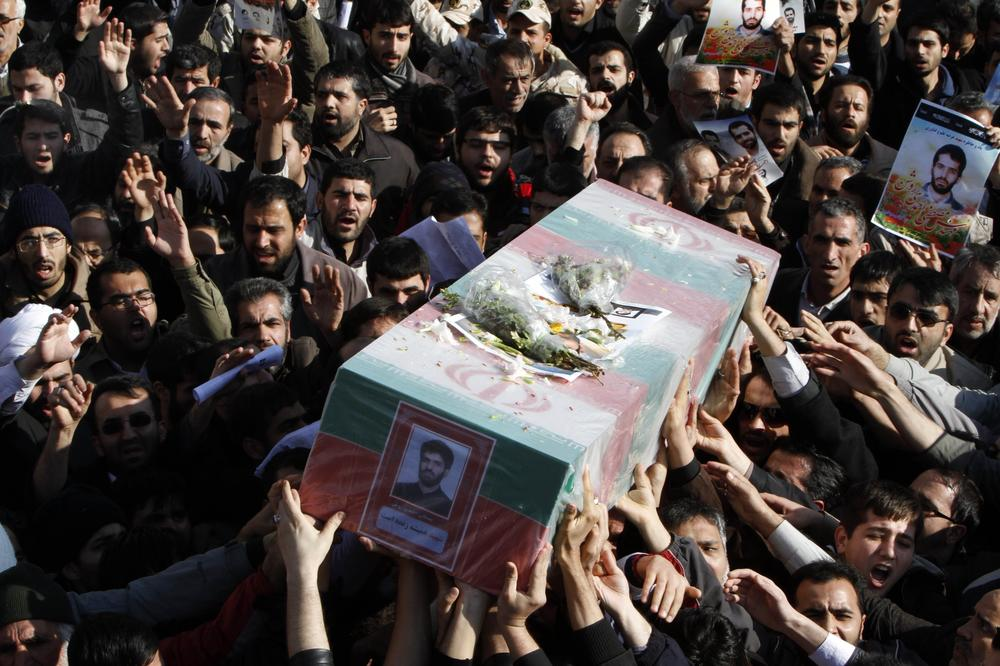 Iranians on Friday carry the flag draped coffin of Mostafa Ahmadi Roshan,a chemistry expert and a director of the Natanz uranium enrichment facility in central Iran, who was killed in a brazen daylight assassination Wednesday in Tehran.(AP)