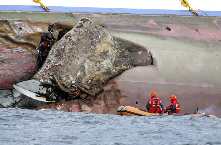 Firefighters on a dinghy look at a rock emerging from the side of the luxury cruise ship Costa Concordia, the day after it ran aground off the Tuscan island of Giglio, Italy, Sunday, Jan. 15. (AP)