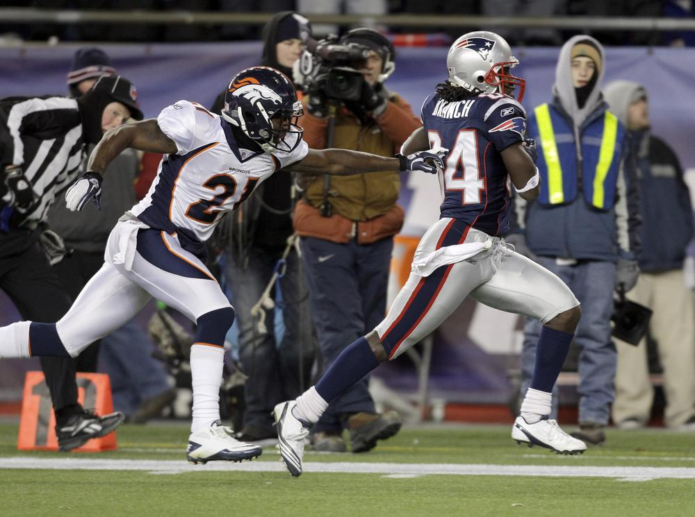 Broncos cornerback Andre' Goodman tries to stop Patriots wide receiver Deion Branch as he scores on a 61-yard touchdown during the first half. (AP)
