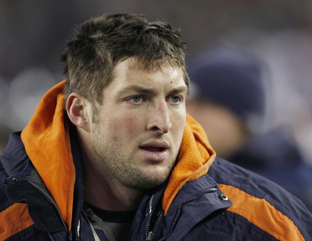 Tim Tebow watches from the sidelines during the first half Saturday. (AP)