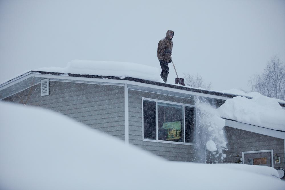 14-year-old Doug Hamrick shovels snow off of his family's roof in Anchorage. (AP)
