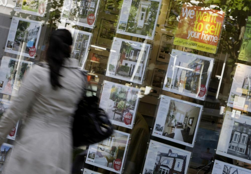 A woman walks past a real estate agent's window in west London. (AP)