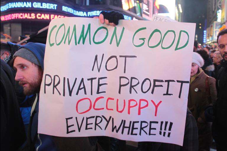 An Occupy Wall Street protester holds a sign as he marches in Times Square in New York, Saturday, Dec. 17, 2011. Earlier in the day dozens of Occupy Wall Street protesters were arrested as they attempted to enter an Episcopal church-owned lot in Manhattan's Tribeca neighborhood. (AP)