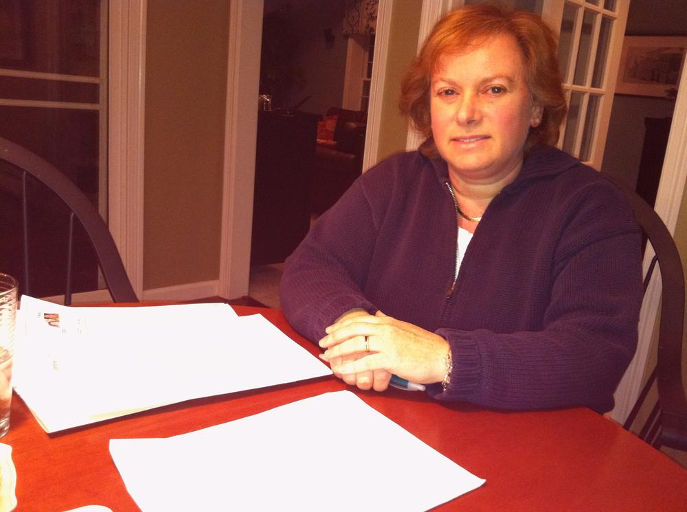 Dr. Sarah Bechta tries to compare tiered health plans. (Martha Bebinger/WBUR)