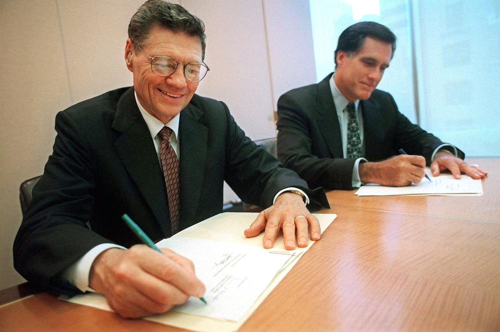 "Thomas S. Monaghan, founder of Domino's Pizza, Inc., left, and Mitt Romney, then-managing director of Bain Capital, Inc., sign an agreement for Monaghan to sell a ""significant portion"" of his stake in the company to Bain Capital, in 1998. (AP)"
