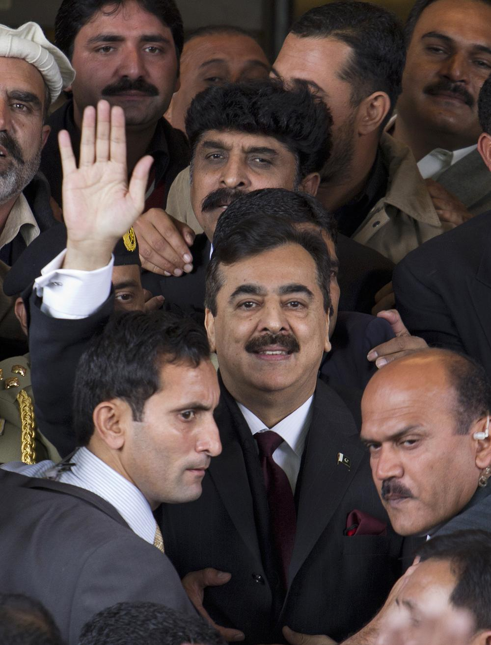Pakistani Prime Minister Yousuf Raza Gilani waves as he leaves the Supreme Court in Islamabad, Pakistan on Thursday. (AP)