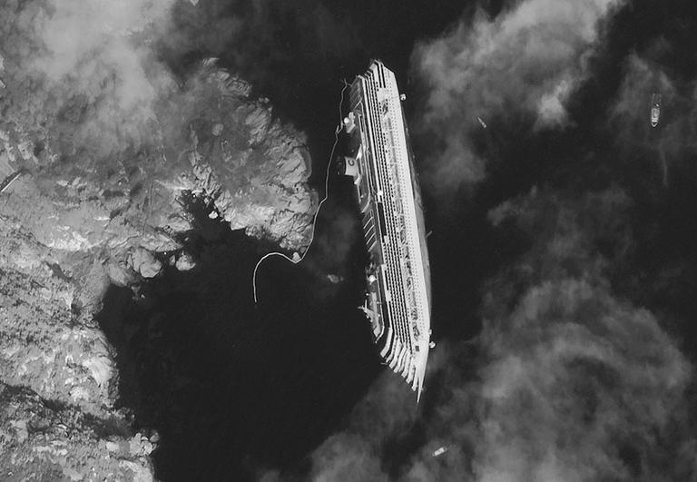 This Jan. 17, 2012 satellite image provided by DigitalGlobe shows the luxury cruise ship Costa Concordia, which ran aground on Friday, Jan. 13, lying on its starboard side just off the tiny Tuscan island of Isola del Giglio, Italy.  (AP Photo/DigitalGlobe)