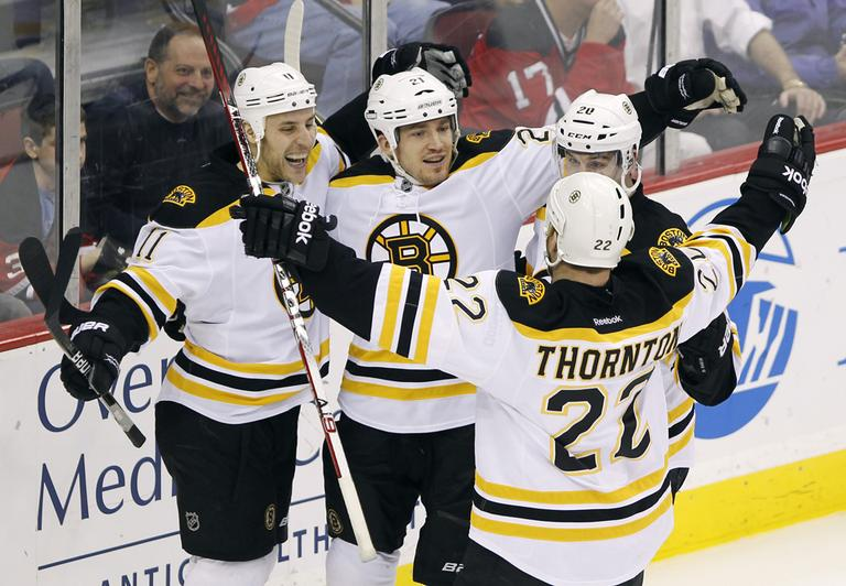 Boston Bruins' Andrew Ference (21) celebrates with Gregory Campbell (11), Daniel Paille (20) and Shawn Thornton (22) after Ference scored in the third period in Newark, N.J., on Thursday. (AP)