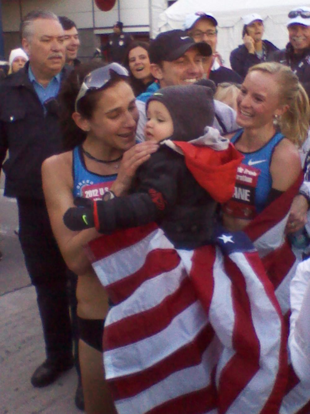 Kara Goucher, holding son Colt, and the women's winner, Shalane Flanagan. (Alex Ashlock/WBUR)