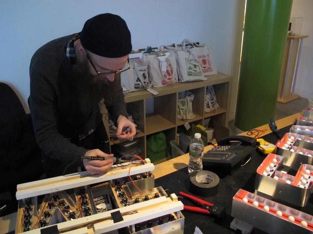 Jamaica Plain artist Steve Lambert prepares his piece for the Biennial. (Andrea Shea/WBUR)
