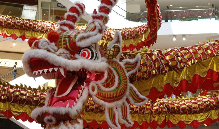 A man walks on an escalator next to a giant dragon decoration for the upcoming Chinese New Year of the Dragon at a shopping mall in Kuala Lumpur, Malaysia, Friday, Jan. 6, 2012. (AP)