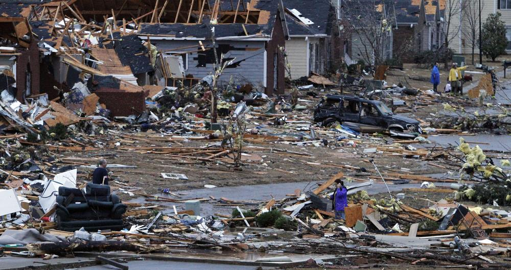 Residents walk around through the debris of their neighborhood after a tornado ripped through the Trussville, Ala. area in the early hours of Monday. (AP)
