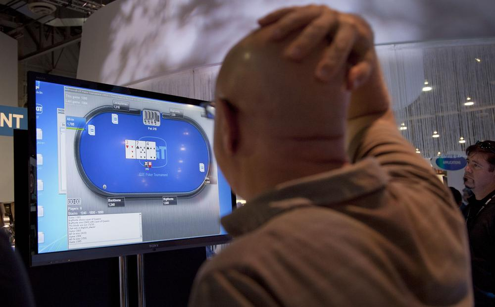 Casino industry representatives and exhibitors watch an online poker game during industry conference in Las Vegas. (AP)