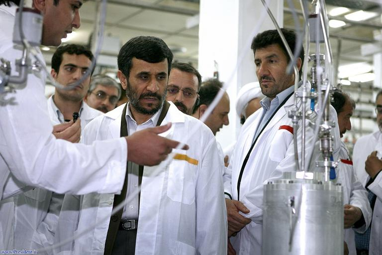 In this photo released by the Iranian President's Office, Iranian President Mahmoud Ahmadinejad, center, listens to a technician during his visit of the Natanz Uranium Enrichment Facility April 8, 2008. (AP)
