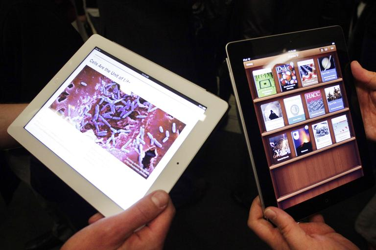 Apple employees demonstrate interactive features of iBooks 2 for iPad, Thursday, Jan. 19, 2012 in New York. IBooks 2 will be able to display books with videos and other interactive features. (AP)