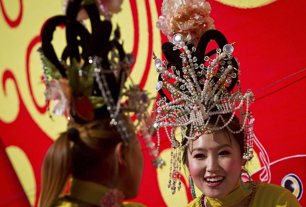Chinese female performers chat near the stage before their show at the Longtan Park's temple fair during the Chinese New Year celebrations in Beijing, China, Wednesday. (AP)