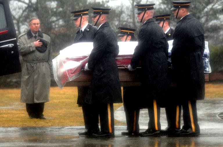 The casket containing the body of Army Spc. Keith Benson is removed from a hearse at the Massachusetts National Cemetery in Bourne Friday. (Courtesy David Curran/SatelliteNewsService.com)