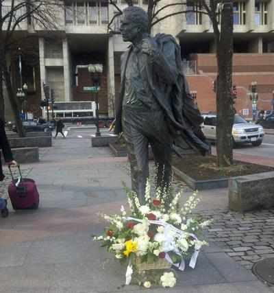 Flowers lay at the foot of Kevin White's statue near Faneuil Hall in Boston. (Lynn Jolicoeur/WBUR)