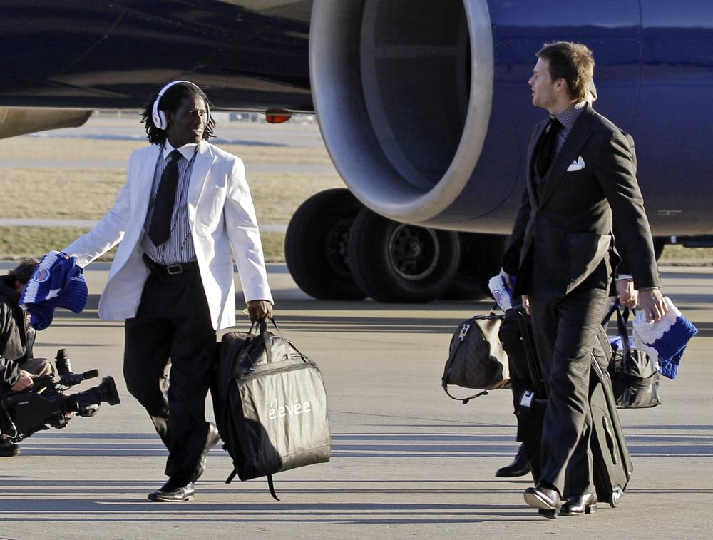 New England Patriots wide receiver Deion Branch, left, talks to Tom Brady as they arrive at the Indianapolis International Airport for Super Bowl XLVI Sunday, in Indianapolis. (AP)