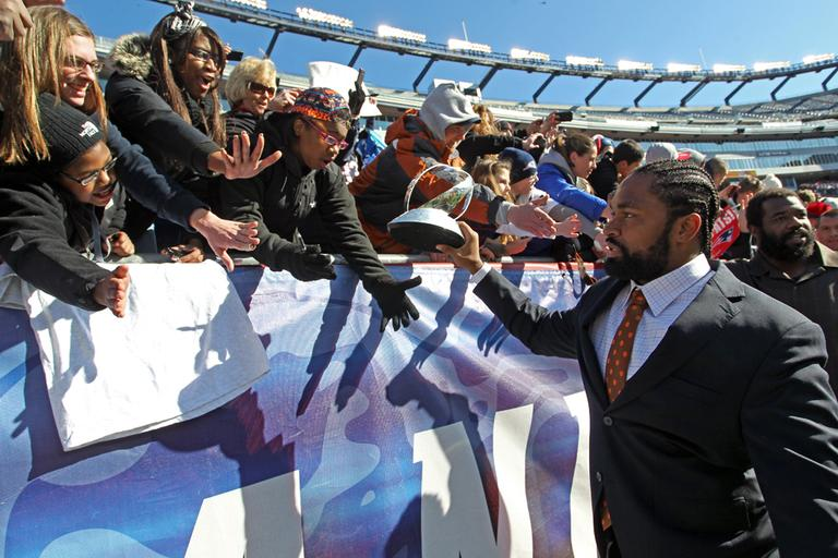 Patriots linebacker Jerod Mayo, front right, displays the Lamar Hunt Trophy to fans as he exits the stadium following a sendoff rally in Foxborough, Sunday. (AP)