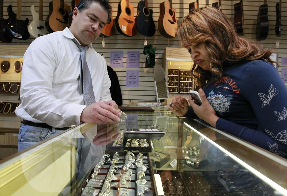 Loan officer and salesman Roy Knudsen, of Boston, left, displays earrings to Doreena Ruiz, of Framingham, Mass., as Ruiz shops at Suffolk Jewelers & Pawnbrokers, in Boston. (AP)
