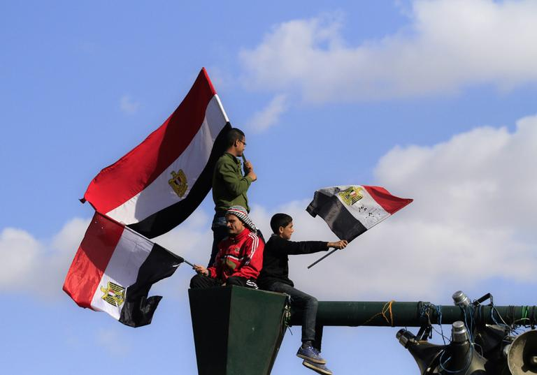"""Egyptians protesters wave the national flag from their perch atop a lamp post at a rally to mark the first anniversary of the """"Friday of Rage,"""" in Tahrir Square, in Cairo, Egypt, Friday, Jan. 27, 2012. Some 10,000 Egyptian protesters converged on Cairo's downtown Tahrir Square to mark the first anniversary of """"Friday of Rage,"""" a key day in the popular uprising that ousted President Hosni Mubarak. (AP)"""