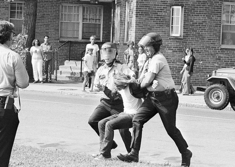 Police take an unidentified youth into custody following stoning of school buses after they had left South Boston High School on the second day of court-ordered busing in Boston, Sept. 14, 1974. (AP)