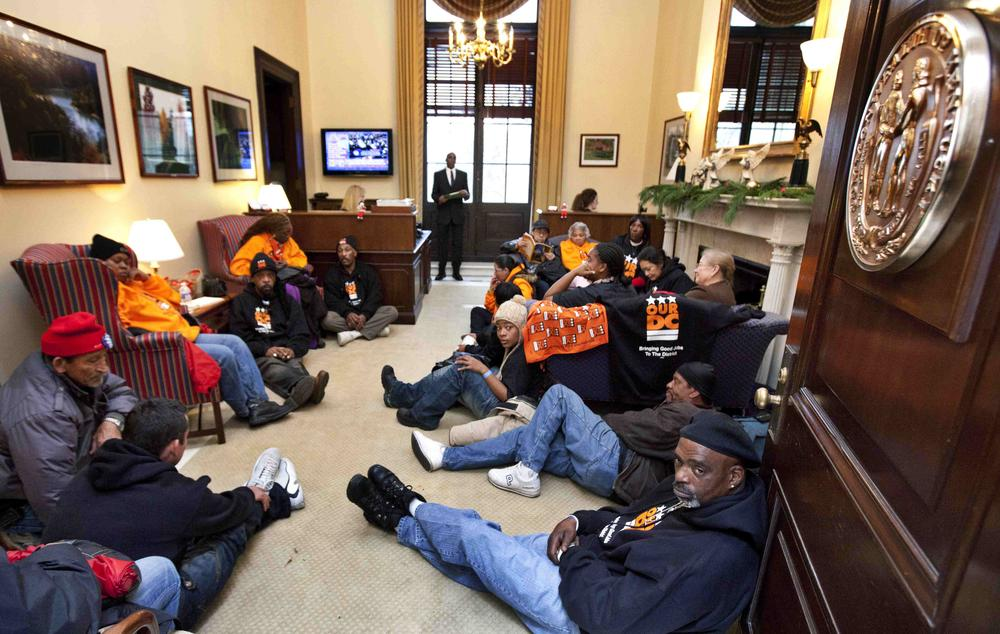 """A protest inside the office of Senate Minority Leader Mitch McConnell of Ky., Tuesday, Dec. 6, 2011, on Capitol Hill in Washington. Protesters are demanding that the lawmakers represent the """"99 percent"""" and not just the corporate lobbyist and and the richest. (AP)"""