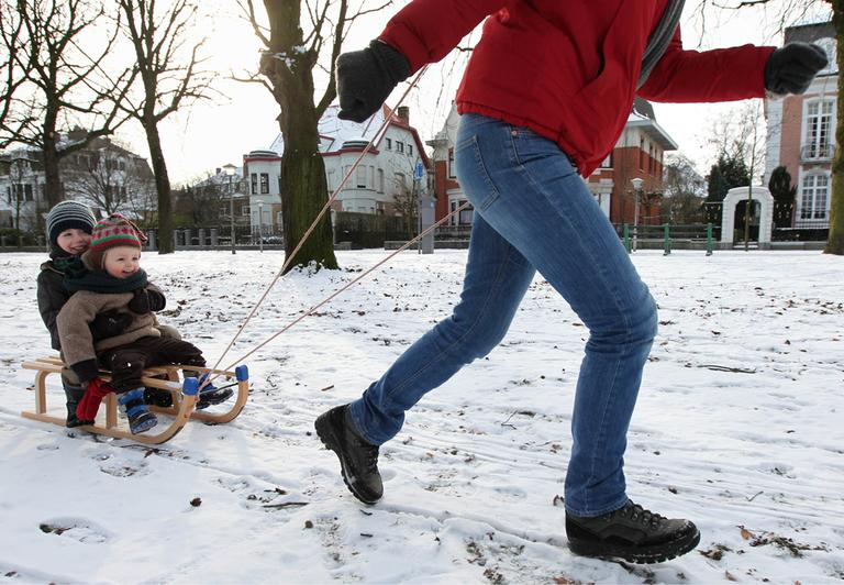 Two children are pulled on a sledge in a park, in Ghent, Belgium, Sunday Feb. 5, 2012. (AP)