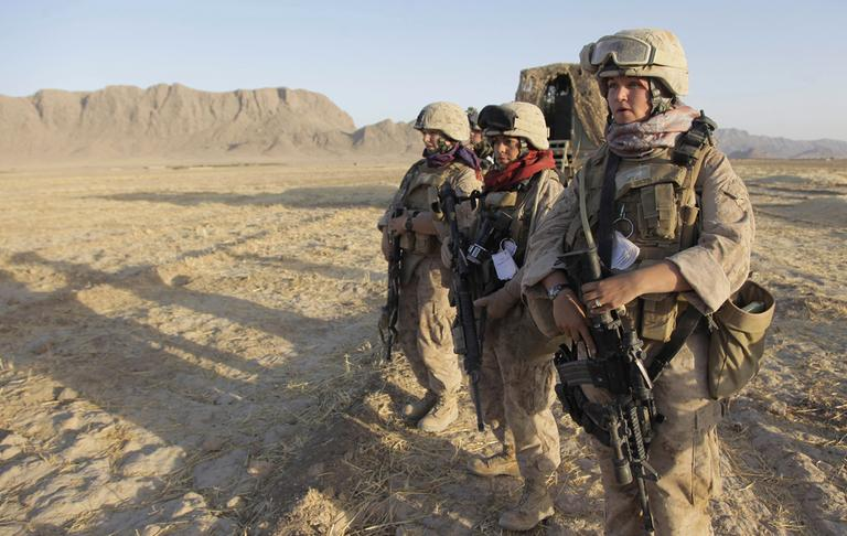 In this Aug. 10, 2009 photo, a U.S. Marine Female Engagement Team wait for the signal to begin their patrol in the Helmand Province of Afghanistan. On Thursday, Feb. 9, 2012, Pentagon rules will catch up a bit with reality, recommending to Congress that women be formally allowed to serve in more jobs closer to the front lines. (AP)