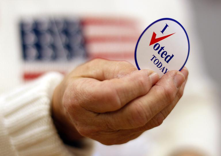 A sticker is handed to a voter on Election Day, Tuesday, Nov. 2, 2010, in Waterville, Maine. (AP)