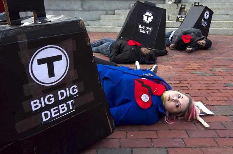 Allison Case, of Boston, front, pretends to be crushed under Big Dig debt, along with other protesters during a demonstration in front of the State House on Feb. 14. (AP)