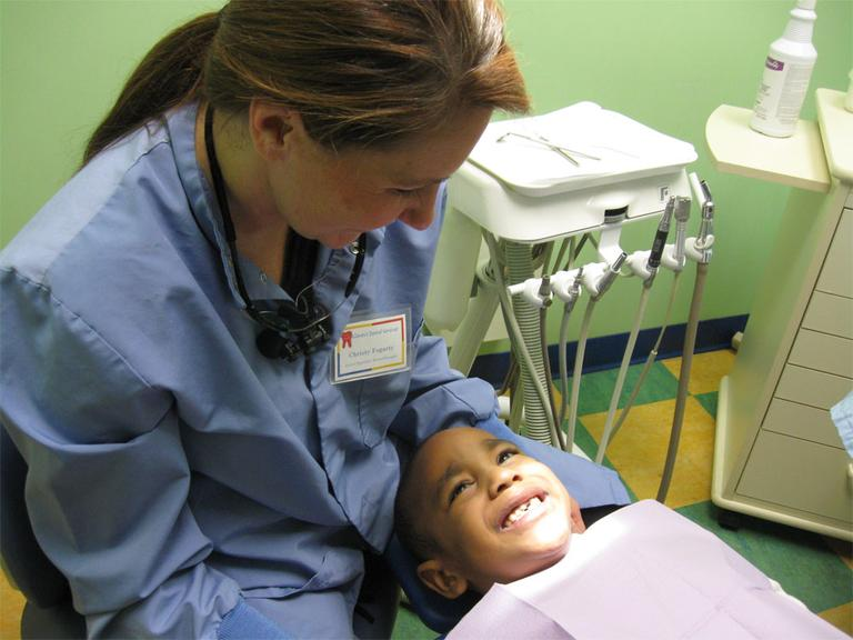 Dental therapist Christy Jo Fogarty gets ready to examine Valentino Cotten in Minneapolis, Minn. (Sasha Aslanian/Minnesota Public Radio)