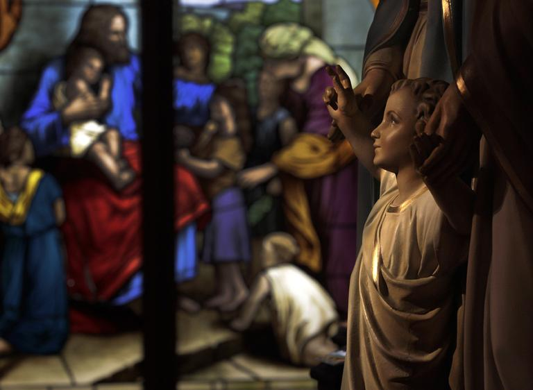 A stained glass window glows, restored and then donated to the Museum of Divine Statues, is seen beyond a statue reclaimed from St. Propcop Church of Cleveland at the museum in Lakewood, Ohio on Tuesday, Dec. 13, 2011. (AP)