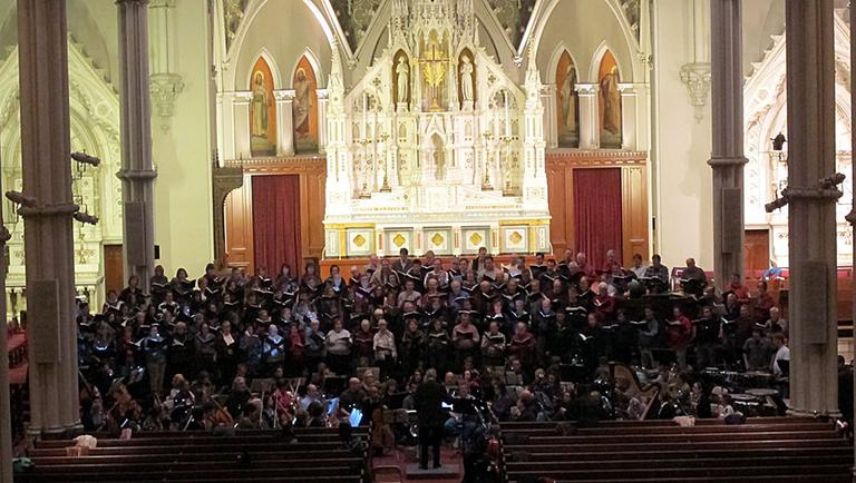 """Richard Pittman directs 300 musicians during a rehearsal of """"War Requiem"""" at the Cathedral of the Holy Cross. (Meghna Chakrabarti/WBUR)"""