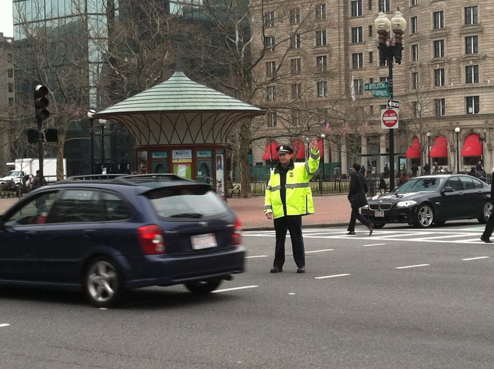 The city has launched an online tool to allow people to report transportation safety concerns for Boston streets. One area that has been reported is the intersection of Boylston and Dartmouth streets in Copley Square.  Pictured: A Boston police officer directs traffic in Copley Square. (Steve Brown/WBUR/FILE)