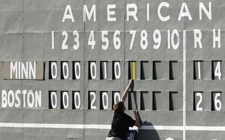 """A scorekeeper adds a run to the board at JetBlue Park in Fort Myers, Fla. The scoreboard is very same manual scoreboard that adorned the original """"Green Monster"""" in Boston for nearly three decades, before being put in storage. (AP)"""