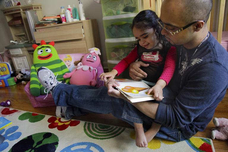 Christopher Astacio reads with his daughter Cristina, 2, recently diagnosed with a mild form of autism, in her bedroom on Wednesday, March 28, 2012 in New York. Autism cases are on the rise again, largely due to wider screening and better diagnosis, federal health officials said Thursday, March 2012. (AP)
