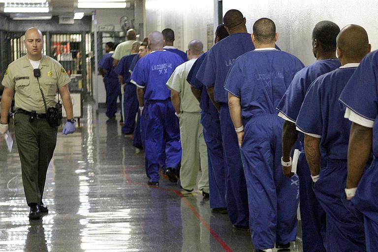 In this Oct. 27, 2011 photo, a deputy passes a line of inmates, as seen during a tour of the Men's Central Jail, run by the Los Angeles County Sheriff's Department, in downtown Los Angeles. (AP)