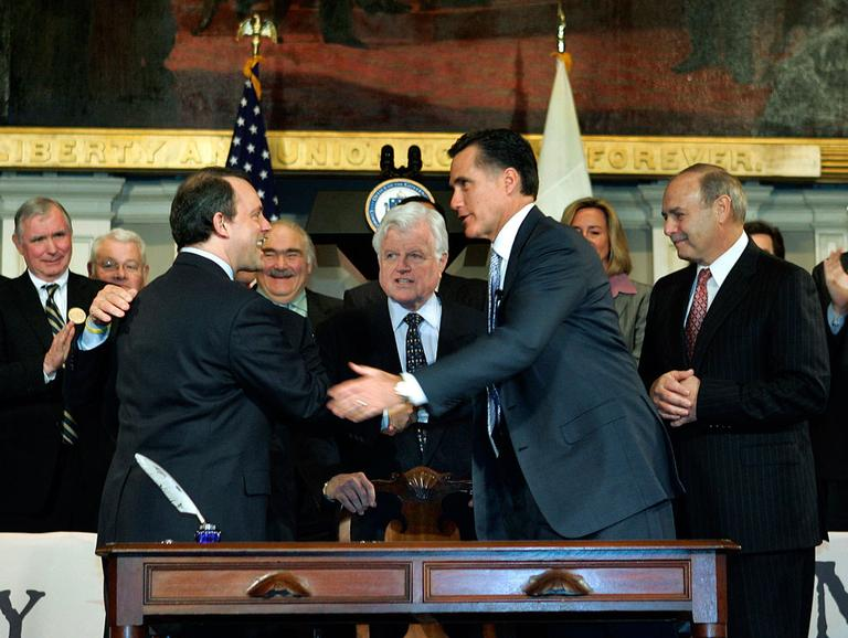 In this April 12, 2006, file photo, then-Gov. Mitt Romney is seen with lawmakers and staffers after signing the state's universal health law at Faneuil Hall in Boston. (AP File)