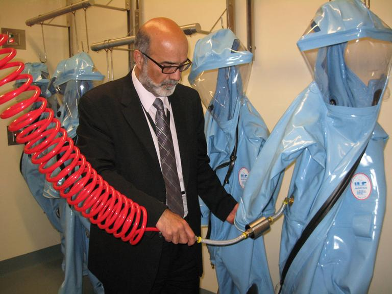 Ara Tahmassian, NEIDL associate director and associate vice president for research compliance at Boston University, demonstrates how biosafety level 4 researchers will hook HEPA air hoses to their protective suits. (Lynn Jolicoeur for WBUR)