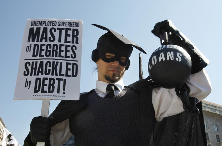 "In this Oct. 6, 2011 photo, Gan Golan, of Los Angeles, dressed as the ""Master of Degrees,"" holds a ball and chain representing his college loan debt, during Occupy DC activities in Washington. (AP)"