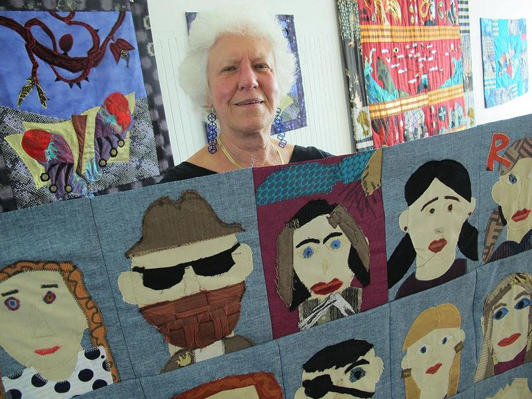 Clara holds up a community self-portrait quilt she created with a class of 15 year-olds. (Andrea Shea/WBUR)