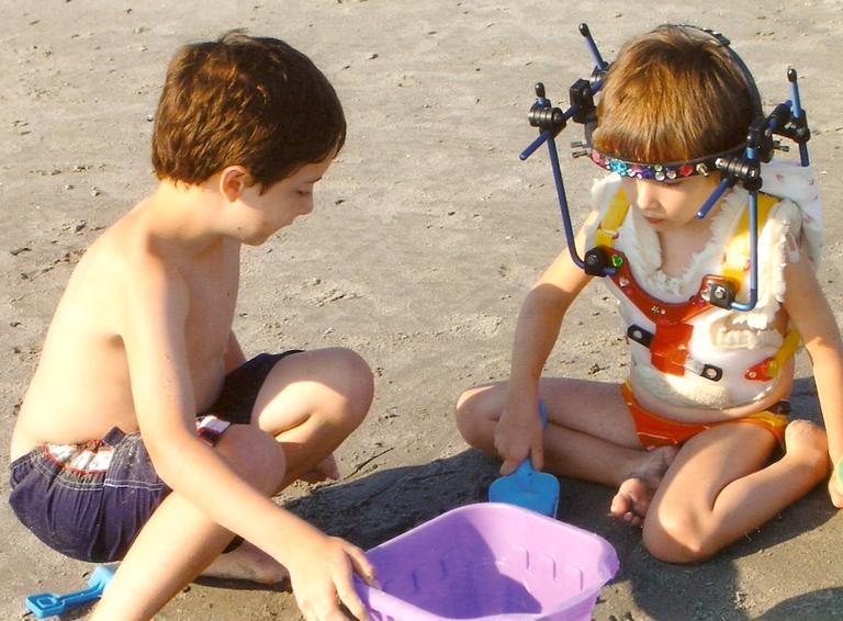 Riley wearing the halo while playing on the beach with her brother Cole (Courtesy of Kristen Davis)