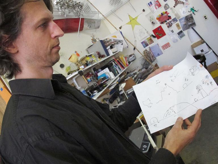 """The Wainwright's son Dedalus, with one of Bill's 'stories."""" Bill uses drawings, along with gestures, to communicate since suffering a stroke. (Andrea Shea/WBUR)"""