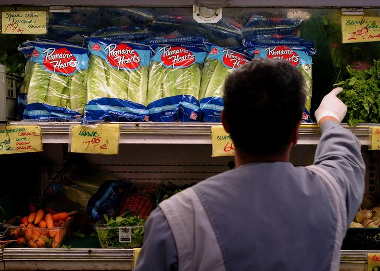 An unidentified produce employee restocks the shelf of bagged lettuce at a grocery store in Berkeley, Calif. (AP)