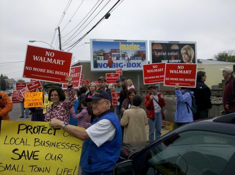 "Sustainable Watertown unveils their new billboard which reads ""Imagine... no big box."" (WBUR/Lynn Jolicoeur)"