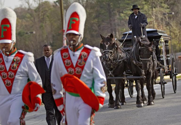 A horse drawn carriage carrying the casket of Florida A&M University band member Robert Champion is lead by his fellow band members following his funeral service Wednesday, Nov. 30, 2011 in Decatur, Ga. The 26-year-old was found dead on Nov. 19 on a bus parked outside an Orlando, Fla. hotel after the school's football team lost to a rival. Authorities suspect hazing but have not released any further details. (AP)