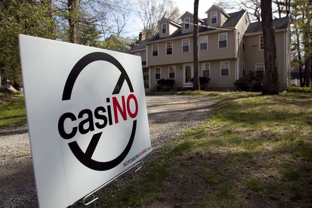 A placard protesting a proposed gambling casino at an unpaved parking lot at Gillette Stadium in Foxborough, Mass. (AP)