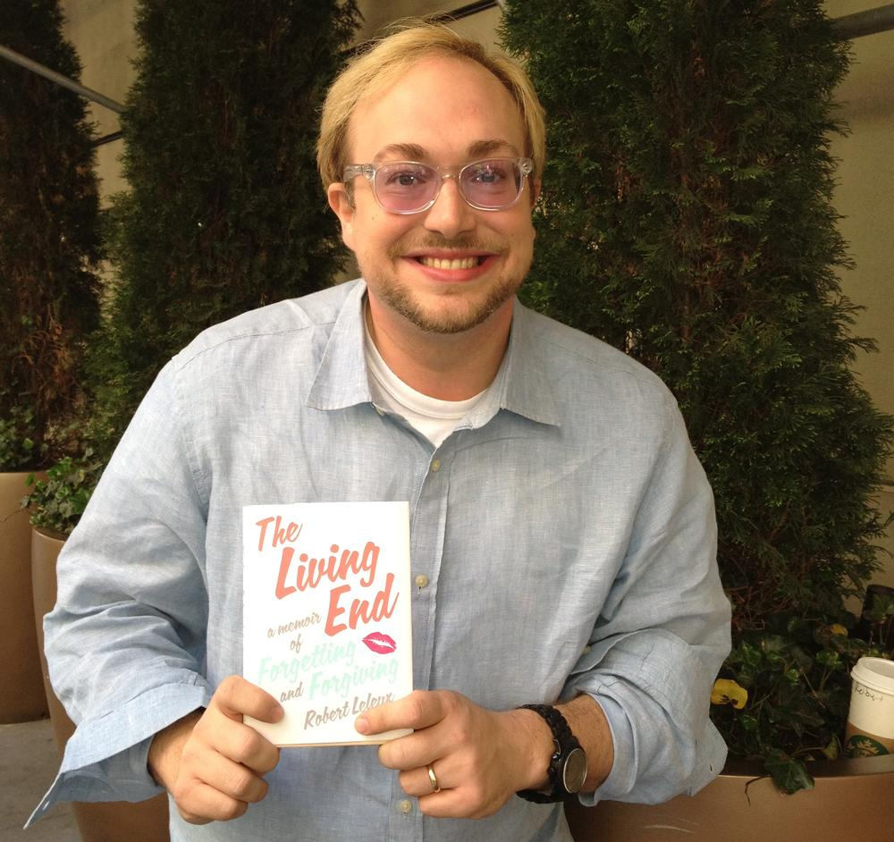 """Author Robert Leleux, holding his book """"The Living End: A Memoir of Forgetting and Forgiving."""" (Robin Young/Here & Now)"""
